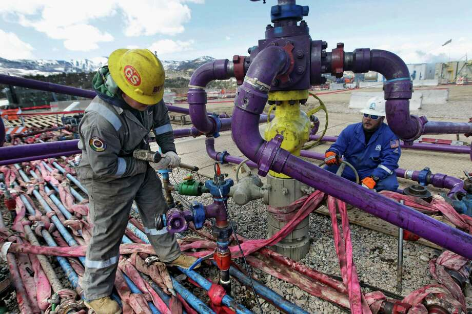 Workers tend to a well head during a hydraulic fracturing operation at an Encana Oil & Gas  gas well outside Rifle, Colo. Analysts expect natural gas prices to rise this year and next. Photo: Brennan Linsley, STF / AP