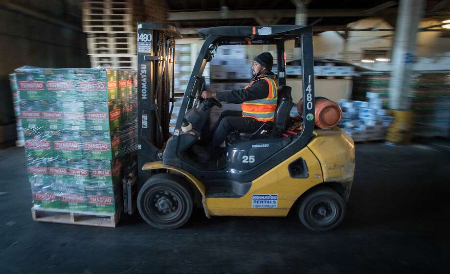 Erasmo Barrera, an employee for Impact Transload and Rail, moves a pallet of beer at the Port of Oakland on January 26, 2017. The port is trying to convince shipping companies arriving from Asia to first visit its facility as a way to boost import business. Photo: JOSH EDELSON, JOSH EDELSON / SAN FRANCISCO CHR