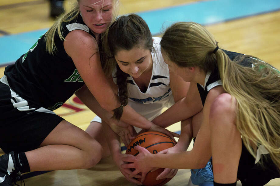 THEOPHIL SYSLO | For the Daily News Meridian's Holly Lavely and Houghton Lake's Lexi Blanchard and Sarah Barnes fight for possession of the ball in a game at Meridian High School on Thursday.
