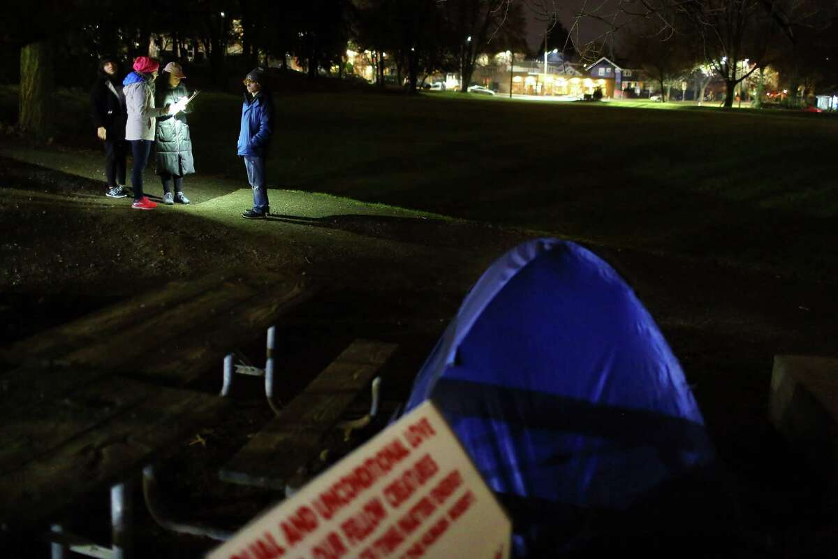 From left, Gina Ohms, Hannah Hunthausen, Jennifer Williams, and Tim Rennaker make note of a tent found in Cowen Park as they look for people sleeping outside during the annual Point in Time count, early Friday morning, Jan. 27, 2017. Around 1,000 volunteers and guides spread out across the city Friday to count the number of people living without shelter.