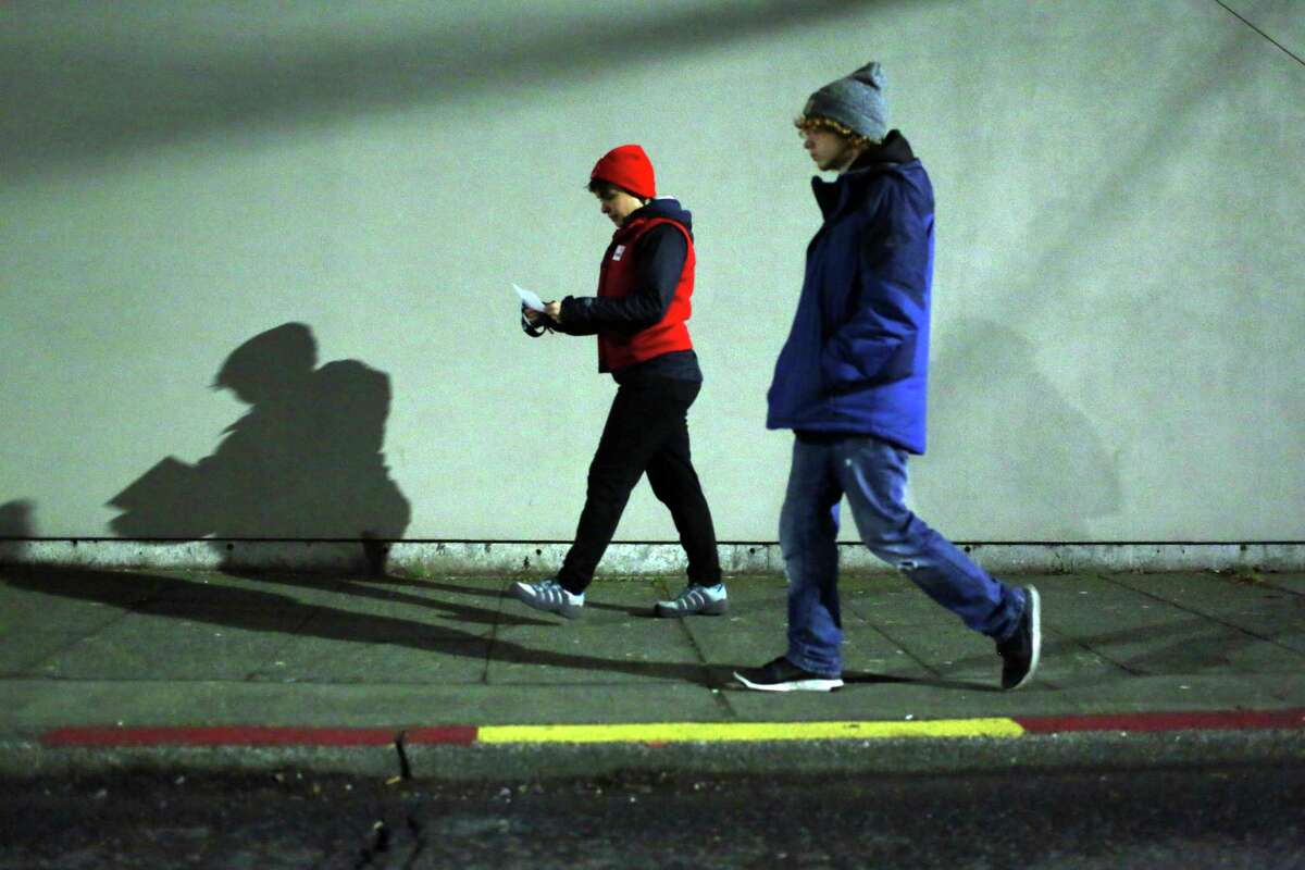 Emily Mirra and and Tim Rennaker walk down NE 65th Street as look for people sleeping outside during the annual Point in Time count, early Friday morning, Jan. 27, 2017. Around 1,000 volunteers and guides spread out across the city Friday to count the number of people living without shelter.