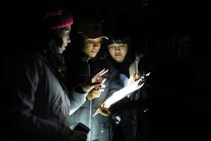 Hannah Hunthausen, left, Jennifer Williams, center and Gina Ohms mark down a tent sighting as they look for people sleeping outside during the annual Point in Time count, early Friday morning, Jan. 27, 2017. Around 1,000 volunteers and guides spread out across the city Friday to count the number of people living without shelter.