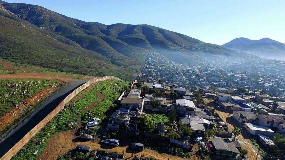 Aerial picture taken with a drone of the urban fencing on the border between the U.S. and Mexico at El Nido del Aguila, at the outskirts of Tijuana, Mexico on Thursday. President Donald Trump's border wall proposal and another to impose a tax on Mexican imports threatens an all-out trade war. Photo: MARIO VAZQUEZ /AFP /Getty Images / AFP or licensors