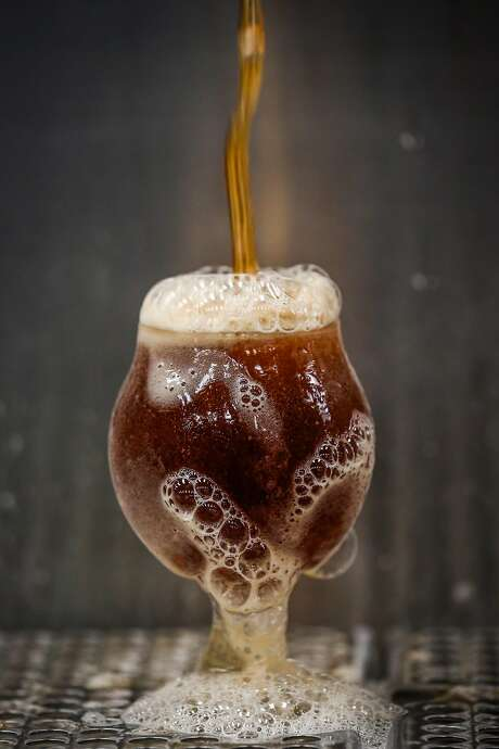 A glass of beer overflows at Barebottle Brewery. Photo: Gabrielle Lurie, The Chronicle