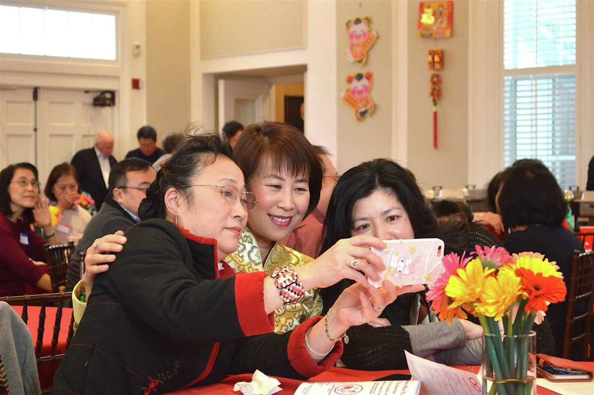 Grabbing a group shot are, from left, Qian Tong and Jamie Zhou of Westport, and Lisa Chen of Fairfield, at the Organization of Chinese-Americans of Fairfield County's Chinese New Year's celebration on Saturday, Jan. 21 at the Westport Woman's Club.