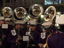 Riordan High School Marching Band plays outside Curran