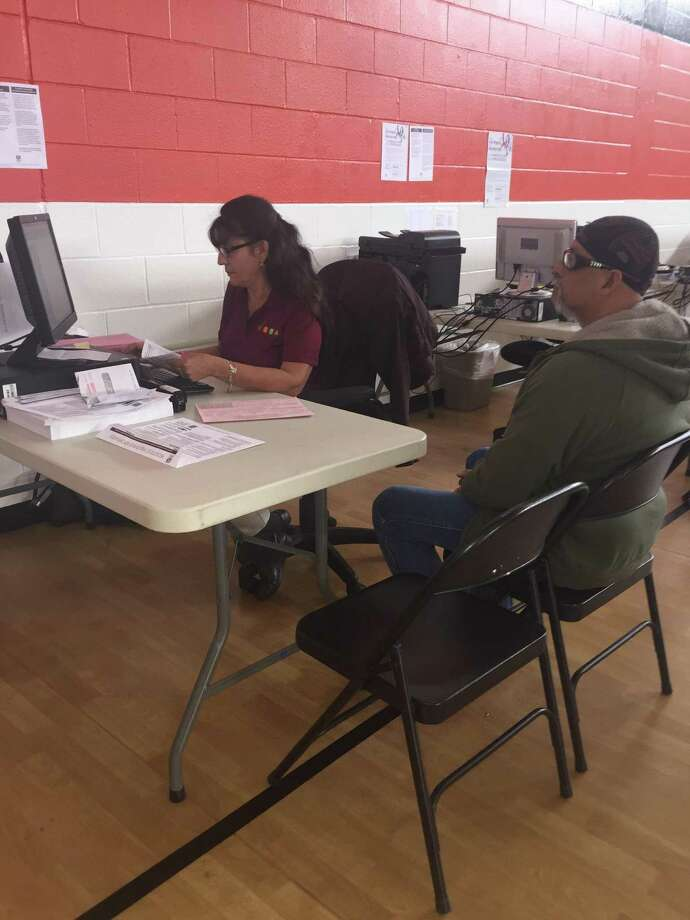 Volunteer Income Tax Assistance volunteer Alma Lopez processes an income tax filing Friday for taxpayer Mario Pina at the YWCA on Castroville Road. Photo: David Hendricks