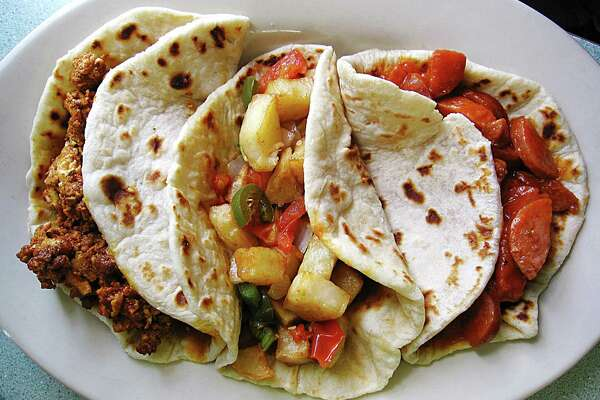 Chorizo and egg, papas rancheras and country guisado tacos on handmade flour tortillas from Mendez Cafe.