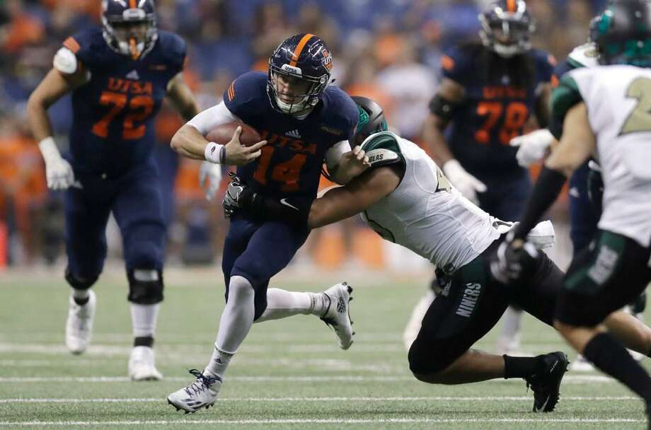 UTSA quarterback Dalton Sturm is hit by Charlotte linebacker Alex Highsmith on Nov. 26, 2016. Adidas has been affiliated with the Roadrunners since the school started playing football. Photo: Eric Gay /Associated Press