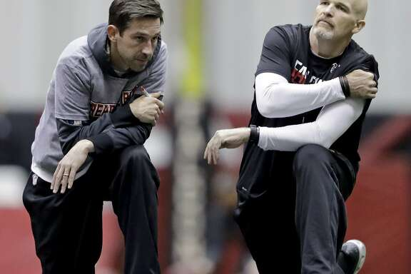 Atlanta Falcons head coach Dan Quinn, right, talks with offensive coordinator Kyle Shanahan during a workout at the NFL football team's practice facility in Flowery Branch, Ga., Friday, Jan. 27, 2017. (AP Photo/David Goldman)