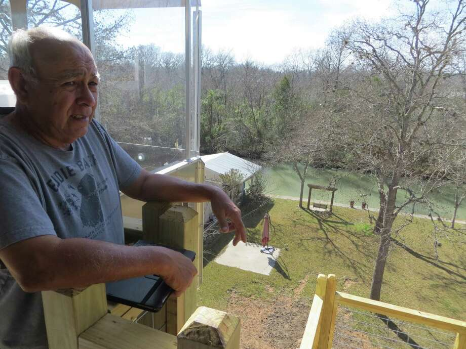Isaac Garcia enjoys the view from the porch on his home overlooking the section of the Guadalupe River known as Lake Placid. The house was raised using a federal flood mitigation grant, but the family says they paid for the elevator at (rear). Photo: Zeke MacCormack / Staff