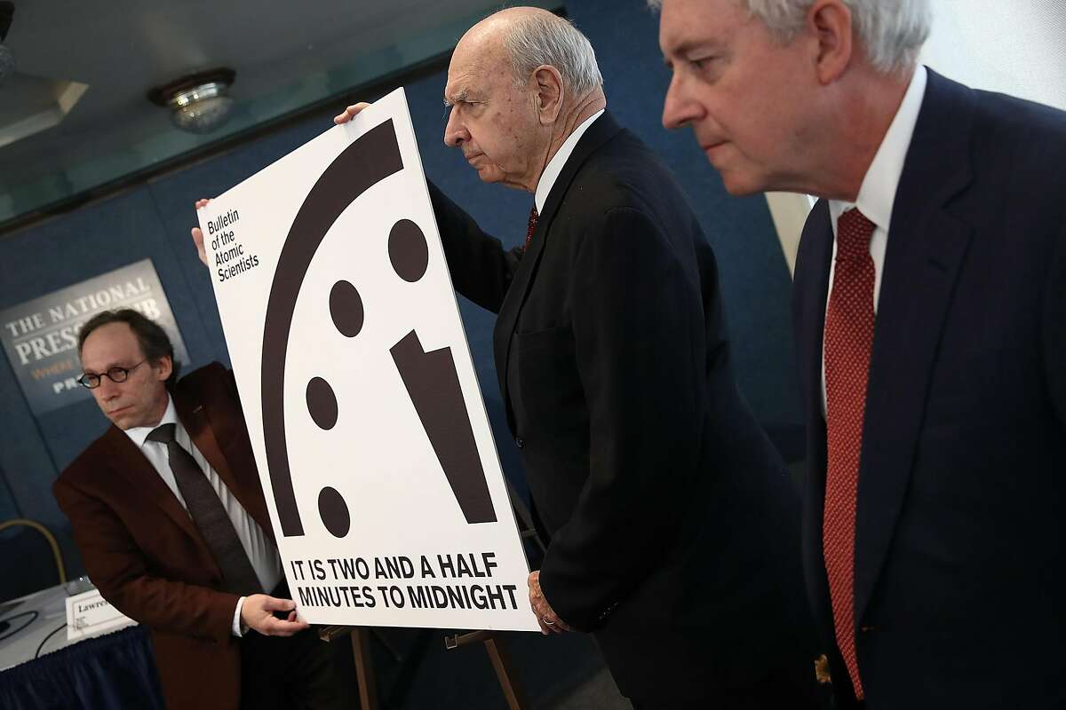 """Members of the Bulletin of Atomic Scientists unveil the 2017 time for the """"Doomsday Clock"""" January 26, 2017 in Washington, DC. For the first time in the 70-year history of the Doomsday Clock, the Bulletin of Atomic Scientists moved the clock forward 30 seconds to two and a half minutes before midnight, citing """"ill-considered"""" statements by U.S. President Donald Trump on nuclear weapons and climate change, developments in Russia, North Korea, India and Pakistan. From left to right are theoretical physicist Lawrence Krauss, former U.S. Ambassador to the United Nations Thomas Pickering and retired U.S. Navy Rear Admiral David Titley."""