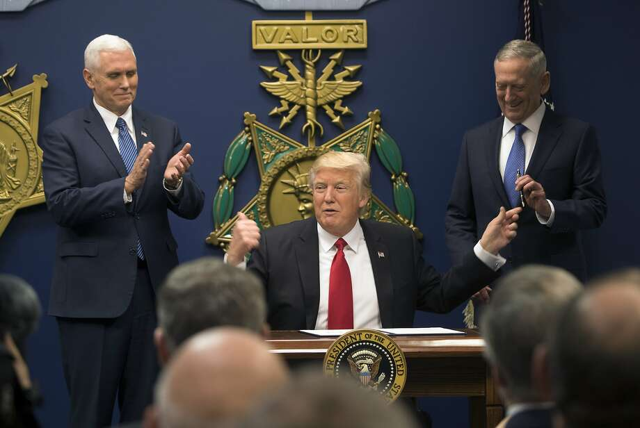 President Donald Trump at the Pentagon, where James Mattis, right, was sworn in as his defense secretary, in Arlington, Va., Jan. 27, 2017. Trump also signed executive orders related to military spending and the vetting of immigrants here on Friday. At left is Vice President Mike Pence. (Stephen Crowley/The New York Times) Photo: STEPHEN CROWLEY, NYT