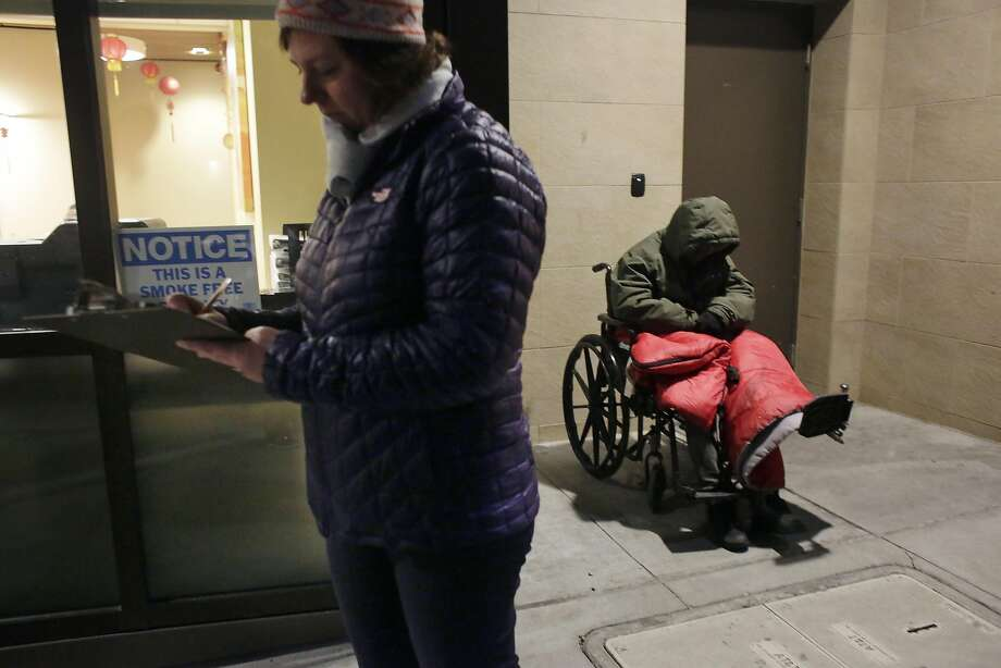 Gigi Whitley, (l to r)�Department of Homelessness and Supportive Housing�deputy director of administration and finance,��marks the tally sheet during the Homeless Point-in-Time Count as Gregory Clark sits in a wheelchair on the street on Thursday, January 26,  2017 in San Francisco, Calif. Photo: Lea Suzuki, The Chronicle