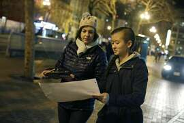 Gigi Whitley, (l to r) Department of Homelessness and Supportive Housing deputy director of administration and finance, and Emma Kositsky, 14,  refer to their group's route map as they walk along Market Street taing a tally of homeless people during the Homeless Point-in-Time Count on Thursday, January 26,  2017 in San Francisco, Calif.
