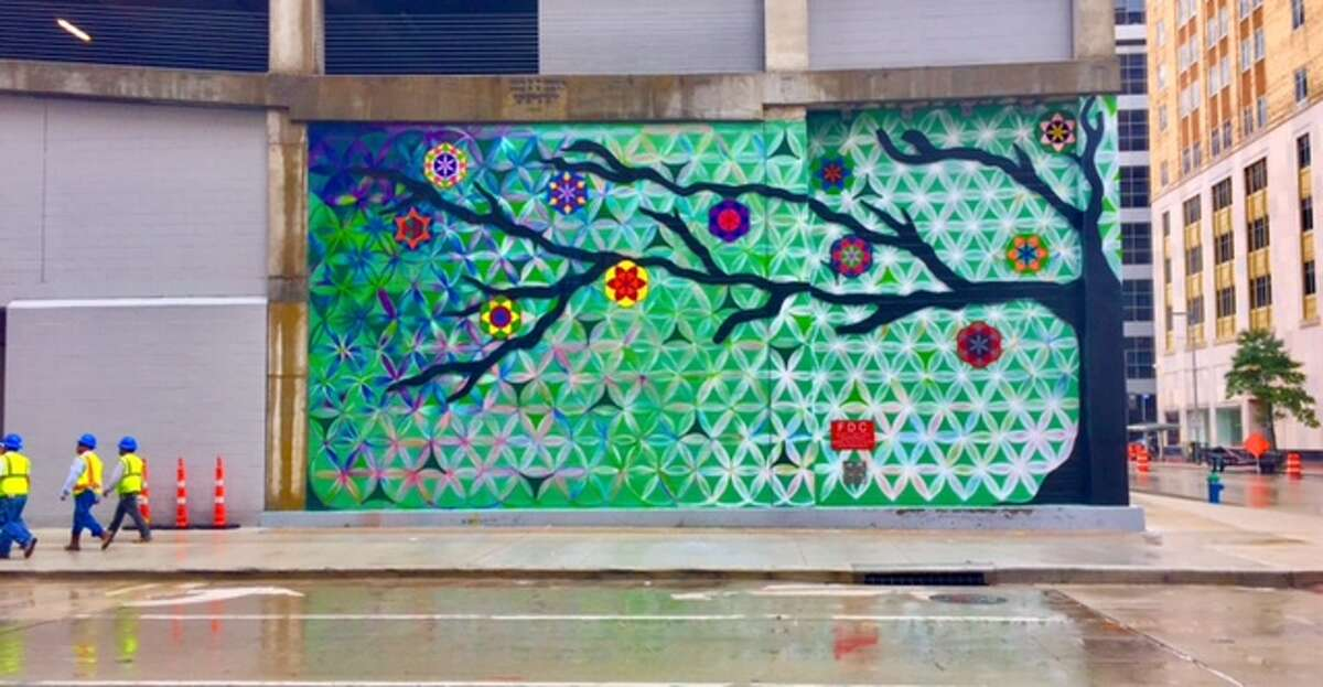 """""""Tree of Life,"""" which wraps around a corner of Capitol Tower downtown, is one of four murals the Super Bowl Host Committee commissioned from Houston artist Reginald Adams."""