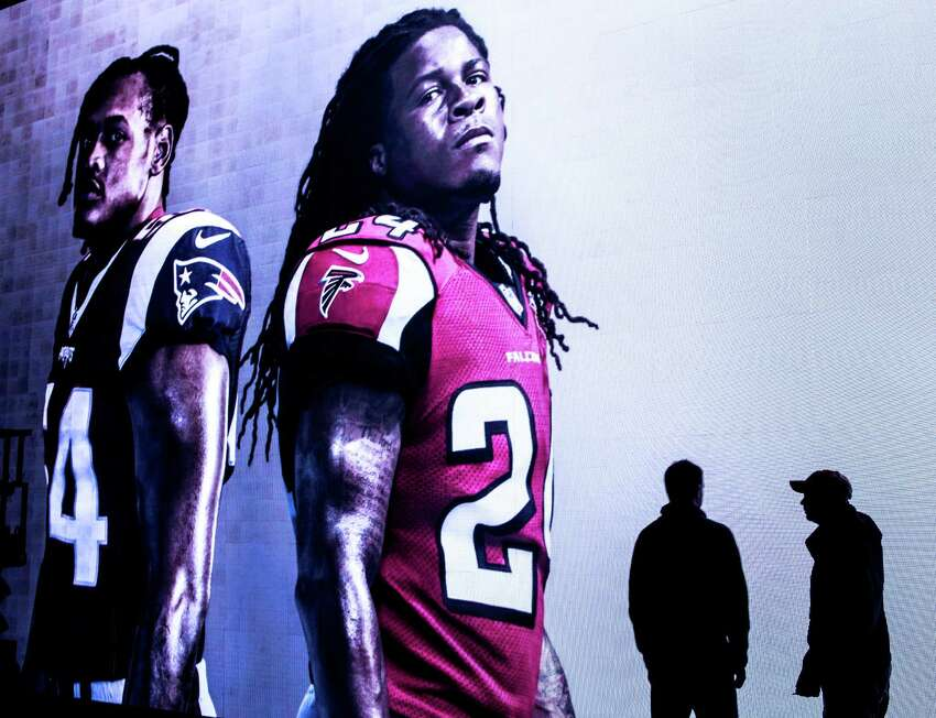 Images of New England Patriots linebacker Dont'a Hightower (54) and Atlanta Falcons running back Devonta Freeman (24) are displayed on a video board at the NFL Experience driven by Genesis at the George R. Brown Convention Center on Friday, Jan. 27, 2017, in Houston. The interactive attraction opens to the public on Saturday.