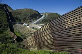 """A U.S. Border Patrol vehicle sits next to a section of the U.S.-Mexico border wall as seen from Tijuana, Mexico, on Thursday, Jan. 26, 2017. U.S. President Donald Trump signed a pair of orders to set in motion the construction of a """"physical wall"""" across the 1,989 mile length of the southern border and to strengthen immigration enforcement within the U.S. Photographer David Maung/Bloomberg"""