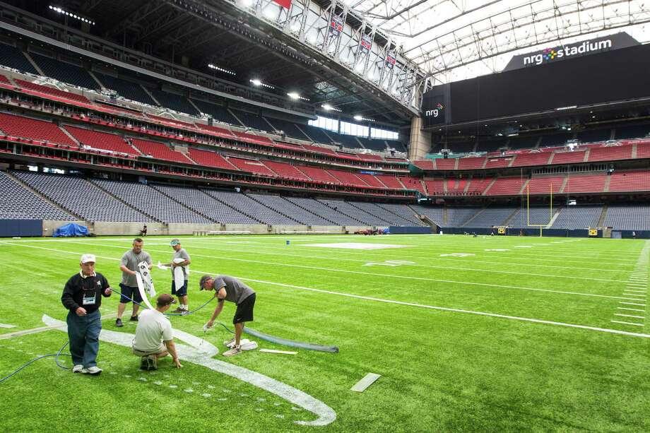 Logos are painted on the turf as NRG Stadium is prepared for Super Bowl LI on Jan. 24. Photo: Brett Coomer, Staff / © 2017 Houston Chronicle