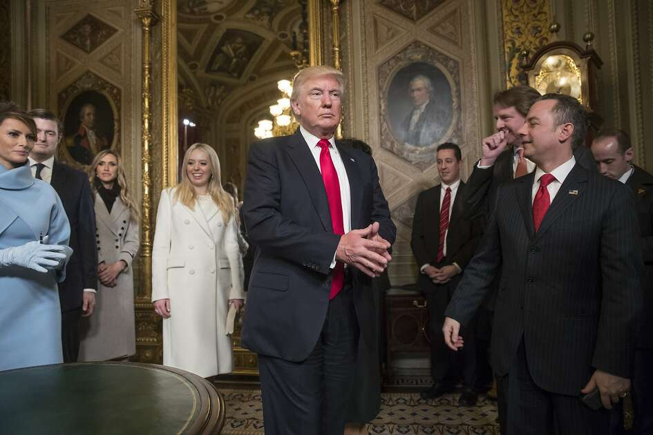 President Donald Trump leaves the President's Room of the Senate on Capitol Hill in Washington, Friday, Jan. 20, 2107, after he formally signed his cabinet nominations into law. He is joined at far left by his wife, first lady Melania Trump and daughter Tiffany Trump. At far right is Chief of Staff Reince Priebus, with White House counsel Donald McGahn, second from right. (AP Photo/J. Scott Applewhite, Pool)