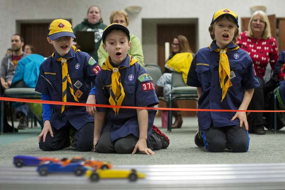 From left, Cub Scout Derek Riter, 8, Wolf Scout Hayden Haller, 8, and Wolf Scout Joshua Ross, 8, watch pinewood derby cars race down the track during one of the heats on Friday at Trinity Lutheran Church. Adams Elementary Boy Scout Troop 3722 raced their pinewood derby cars, while the girl scouts will race them at the church on Saturday. Photo: Erin Kirkland/Midland Daily News/Erin Kirkland