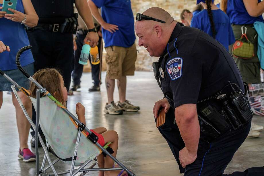 A deputy with the Montgomery County Precinct 3 Constable's Office chats with a young girl during an Americans Stand United rally in Magnolia on July 31, 2016. Photo: Submitted Photo / Michael Murphy - 2016