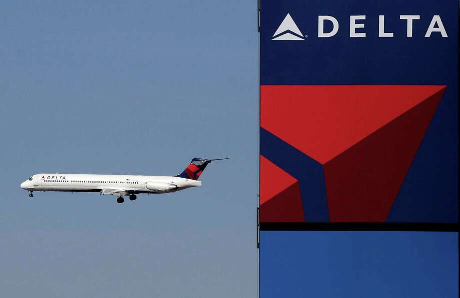 FILE - In this Saturday, April 6, 2013, file photo, a Delta Airlines jet flies past the company's billboard at Citi Field, in New York. The Associated Press reported Wednesdya that a Seattle-bound flight from New York made an emergency landing in Montana after the plane's bathrooms malfunctioned and passengers couldn't hold it anymore. (AP Photo/Mark Lennihan, File) ORG XMIT: CAET706 Photo: Mark Lennihan / Copyright 2017 The Associated Press. All rights reserved.