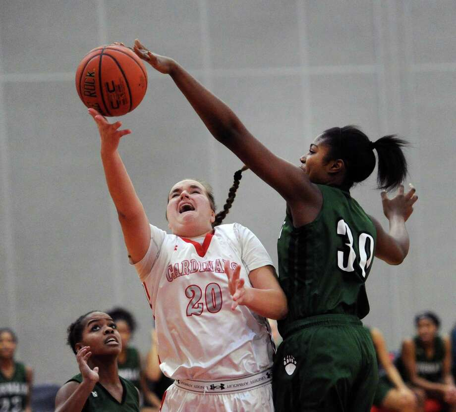 At center, Emily Anderson (20) of Greenwich just gets off a shot as she is fouled by Norwalk's Sarah St. Surin (30), right, during the girls high school basketball game between Greenwich High School and Norwalk High School at Greenwich, Conn., Friday night, Jan. 27, 2017. Photo: Bob Luckey Jr. / Hearst Connecticut Media / Greenwich Time
