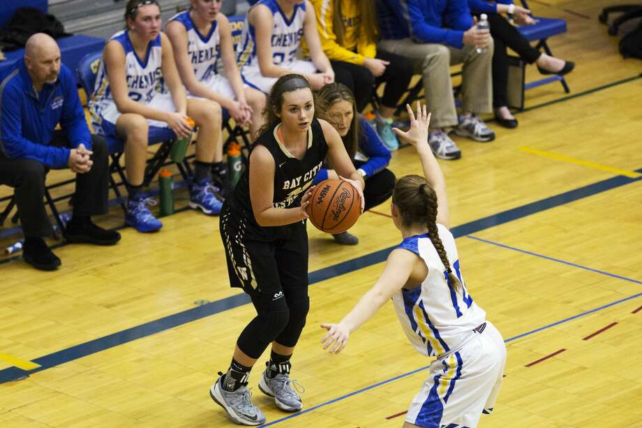 Bay City Western's McKenna Walker shoots the ball while being defended by Midland's Skylar Howard in a game at Midland on Friday. Photo: Theophil Syslo For The Daily News