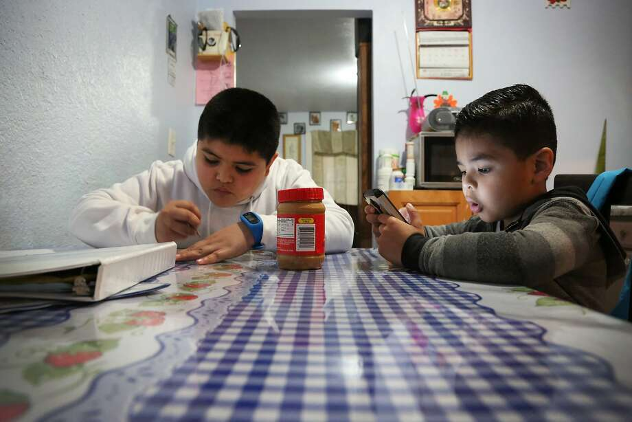 Edwin Bernal (left) hangs out with brother, Angel. Edwin, who suffers from periodic ear infections, may lose health care coverage if the Affordable Care Act is repealed. Photo: Maria J. Alvia/CALmatters