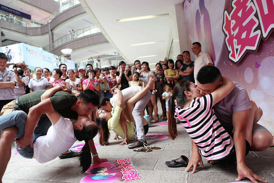 In Chongqing, 20 couples compete in a kissing contest at the New Century Department Store in Yongchuan Shopping Center. The winning couple beat others with 56 minute of kissing in seven rounds with different postures. Photo: Getty Images, Visual China Group / 2015 Visual China Group