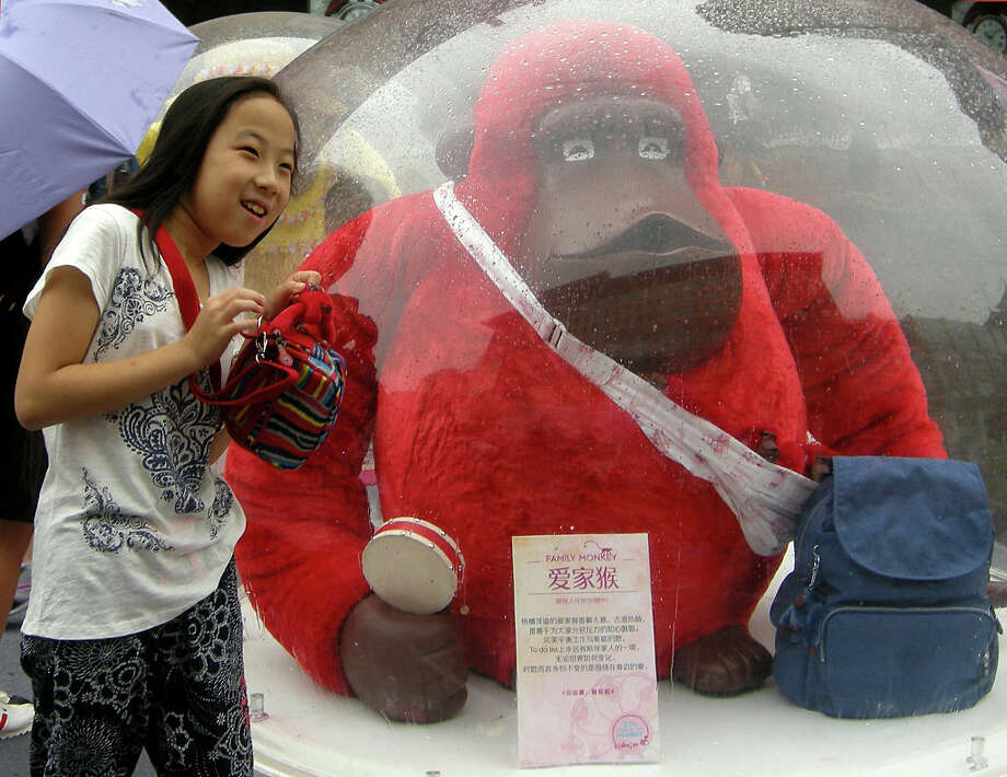 In Beijing, a girl poses with a cartoon monkey in front of Wangfujing department store. The leisure bag brand Kipling's monkey exhibit was a hit with tourists. Photo: Getty Images, Visual China Group / 2016 VCG