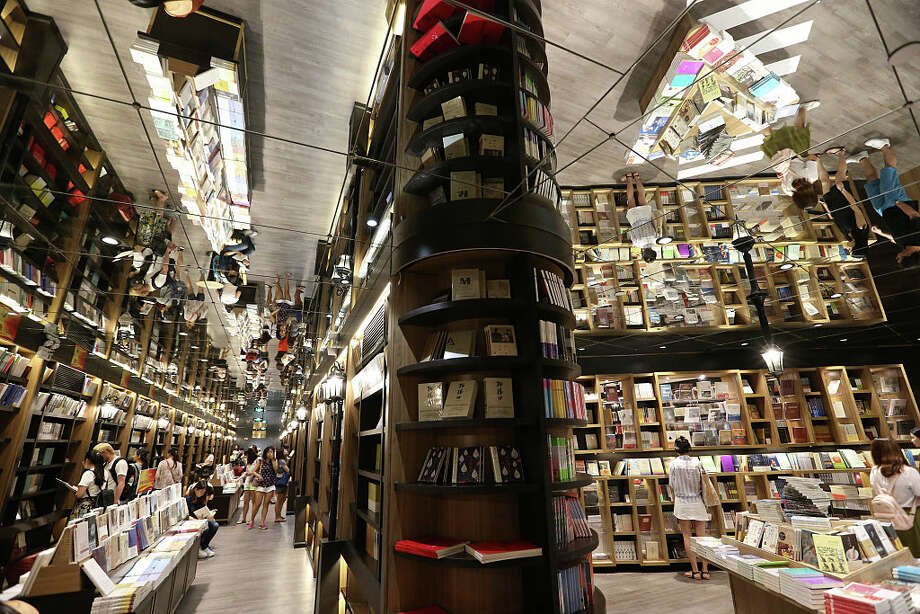 The new Zhongshuge bookstore at Reel Department store in Shanghai, China. The bookstore chain goes to great lengths to make itself attractive: Interior wooden shelves are painted in a spectrum of bright colors, and ceiling lights are arranged to suggest a starry sky. Photo: Getty Images, Visual China Group / 2016 VCG