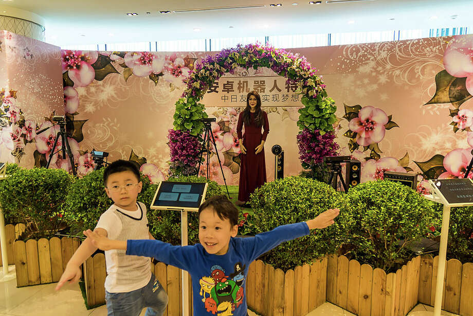 At the Takashimaya Department Store in Shanghai, children react in front to an android that could speak, sing, shake hands and hug with people. Photo: Getty Images, Visual China Group / 2015 Visual China Group