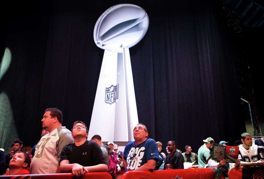 Football fans line up to have their photo taken with the Vince Lombardi Trophy during Super Bowl LI activities at the NFL Experience in the George R. Brown Convention Center on Saturday, Jan. 28, 2017, in Houston. Photo: Brett Coomer, Houston Chronicle / © 2017 Houston Chronicle