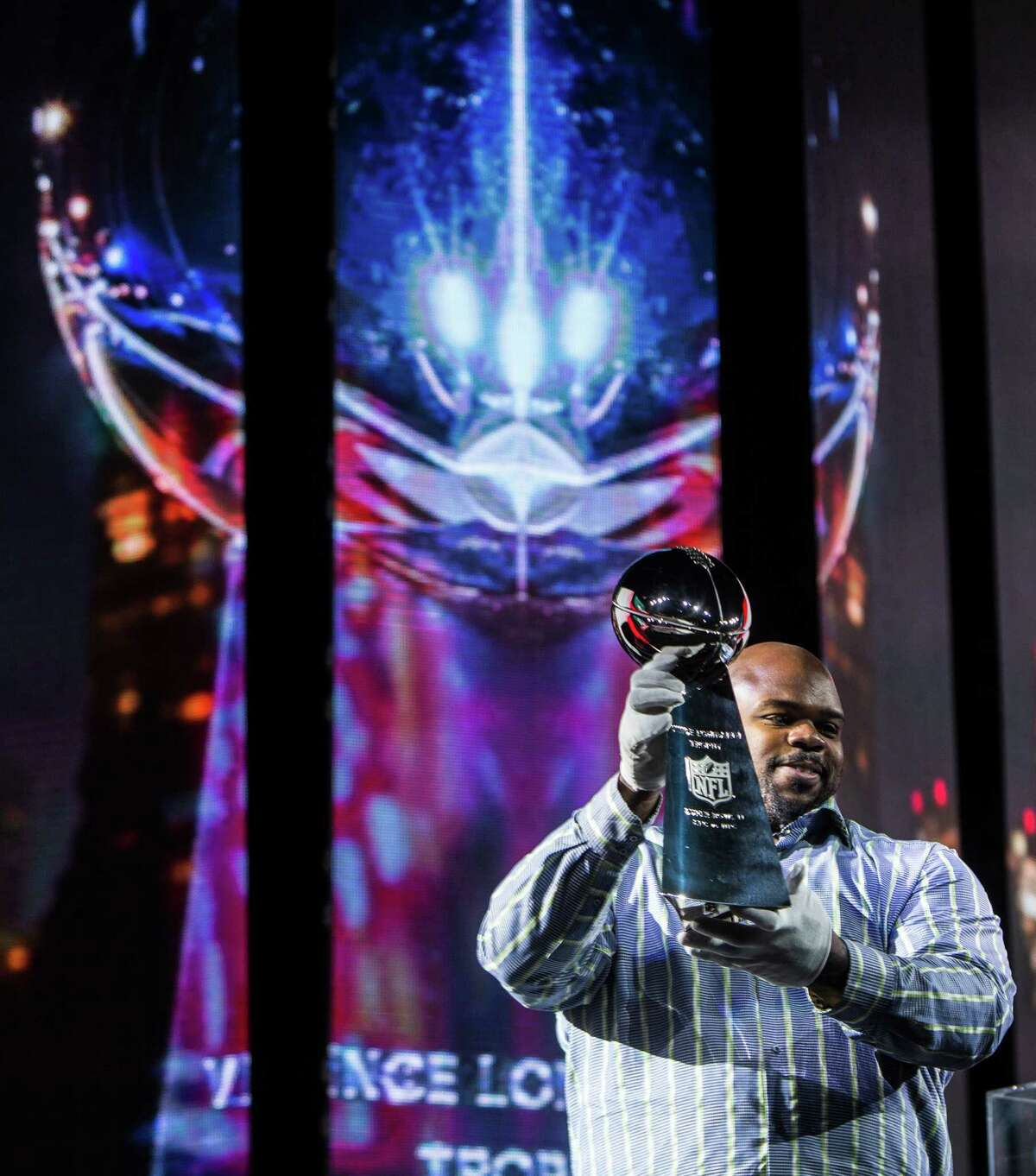Houston Texans nose tackle Vince Wilfork raises the Vince Lombardi Trophy as he delivers it to the George R. Brown Convention Center during Super Bowl LI activities at the NFL Experience on Saturday, Jan. 28, 2017, in Houston.
