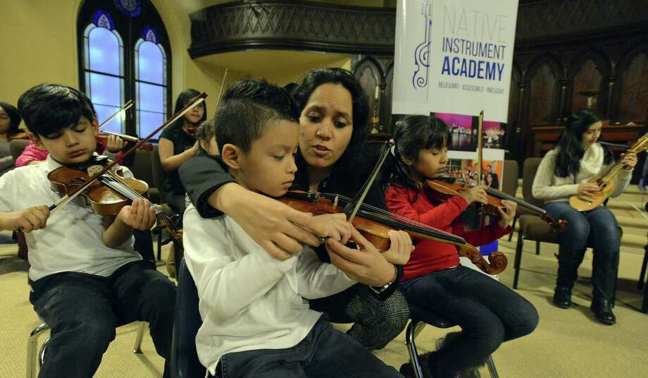 Angelica Durrell, founder and executive director of the INTAKE Music program, works with JenCarlos Aguilar, 6, of Stamford, on proper violin posture during a music class Friday at the Unitarian Universalist Church in Stamford. President Donald Trump's plan to eliminate the National Endowment for the Arts could hurt the music program that receives NEA funding indirectly through the state's Department of Economic and Community Development. Photo: Matthew Brown / Hearst Connecticut Media / Stamford Advocate