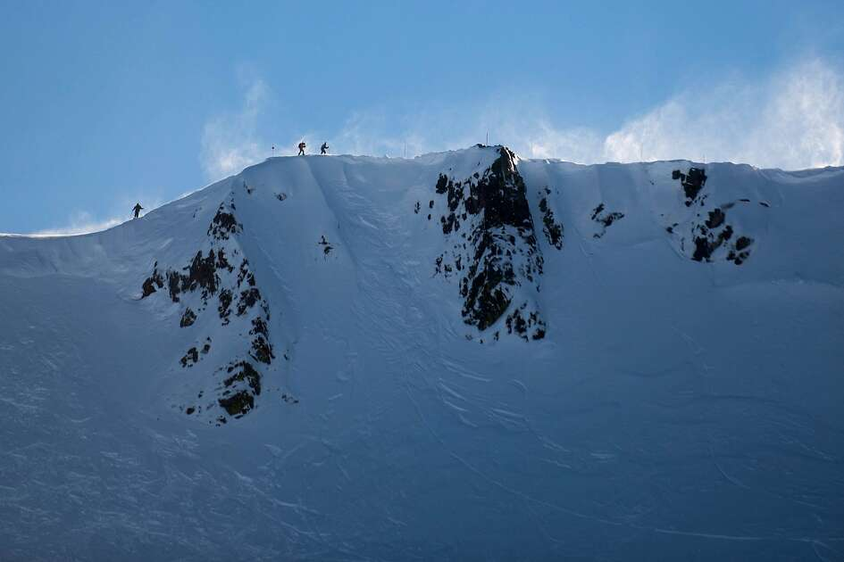 Skiers are seen atop a steep mountain at Squaw Ski Resort in North Lake Tahoe, California on January 27, 2017.  On Tuesday, Joe Zuiches, a ski safety patroller, was killed from a hand-charge explosion during avalanche control activities at Squaw Valley ski resort, the third explosive-caused avalanche death in 43 years.