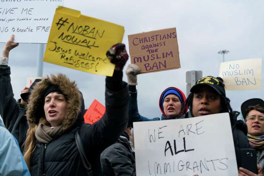 Protesters assemble at John F. Kennedy International Airport in New York, Saturday, Jan. 28, 2017 after two Iraqi refugees were detained while trying to enter the country. On Friday, Jan. 27, President Donald Trump signed an executive order suspending all immigration from countries with terrorism concerns for 90 days. Countries included in the ban are Iraq, Syria, Iran, Sudan, Libya, Somalia and Yemen, which are all Muslim-majority nations. (AP Photo/Craig Ruttle) Photo: Craig Ruttle, Associated Press / FR61802 AP