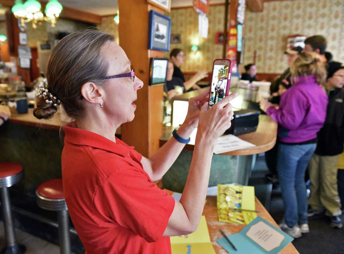 Mary Zautner Smart , sister of ailing Toll Gate Ice Cream owner Rob Zautner, photographs the crowd as they give away free ice cream as a thank you to customers for their support of her brother Saturday Jan. 28, 2017 in Slingerlands, NY. Family members remind the public that their closing will only by temporary. (John Carl D'Annibale / Times Union)