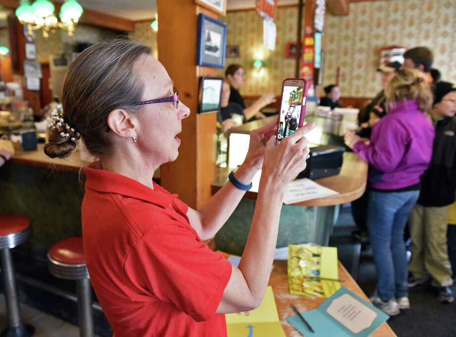 Mary Zautner Smart , sister of ailing Toll Gate Ice Cream owner Rob Zautner, photographs the crowd as they give away free ice cream as a thank you to customers for their support of her brother Saturday Jan. 28, 2017 in Slingerlands, NY. Family members remind the public that their closing will only by temporary.  (John Carl D'Annibale / Times Union) Photo: John Carl D'Annibale / 20039514A