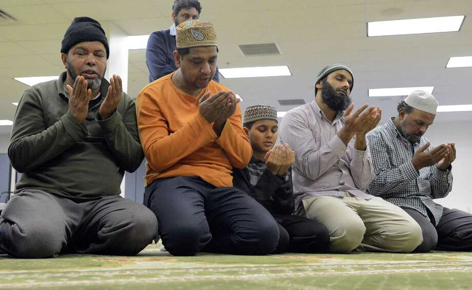 A group of men kneel before the Mehrab as they take evening prayers at the Stamford Islamic Center on Dec. 29, 2016. Photo: Matthew Brown / Hearst Connecticut Media / Stamford Advocate