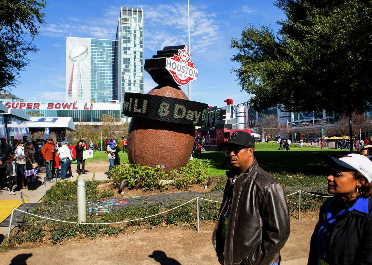 Visitors to Super Bowl Live at Discovery Green walk through the park on Saturday, Jan. 28, 2017, in Houston.