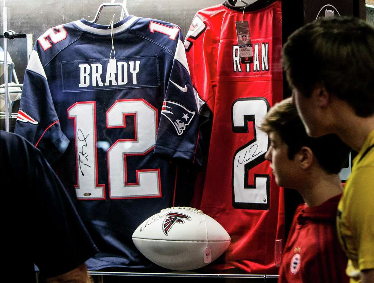 Autographed football jerseys, autographed by New England Patriots quarterback Toma Brady and Atlanta Falcons quarterback Matt Ryan on on display at the NFL Experience inside the George R. Brown Convention Center on Saturday, Jan. 28, 2017, in Houston.
