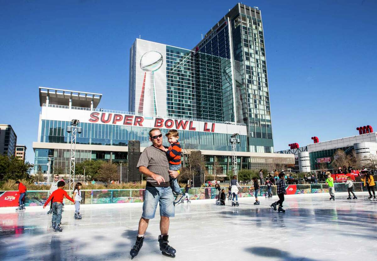 Skaters take a turn on the ice rink below a large image of the Vince Lombardi Trophy while visiting Super Bowl Live at Discovery Green on Saturday, Jan. 28, 2017, in Houston.