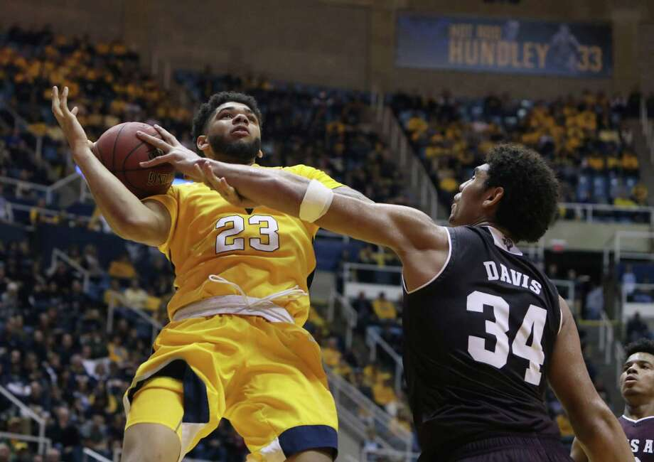 Texas A&M center Tyler Davis (34) fouls West Virginia forward Esa Ahmad (23) as he drives to the basket during the second half of an NCAA college basketball game, Saturday, Jan. 28, 2017, in Morgantown, W.Va. (AP Photo/Raymond Thompson) Photo: Ray Thompson, Associated Press / FR171247 AP