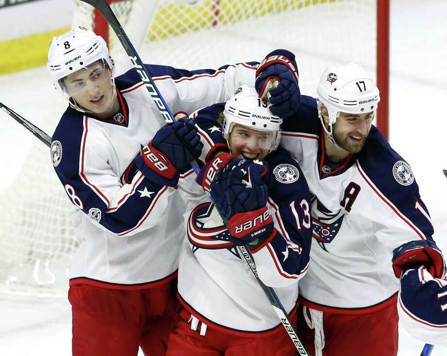Columbus Blue Jackets' Cam Atkinson (13) celebrates his overtime goal with teammates Brandon Dubinsky (17) and Zach Werenski (8) during a game in Ottawa, Ontario on Jan. 22. Photo: Fred Chartrand / Associated Press / The Canadian Press