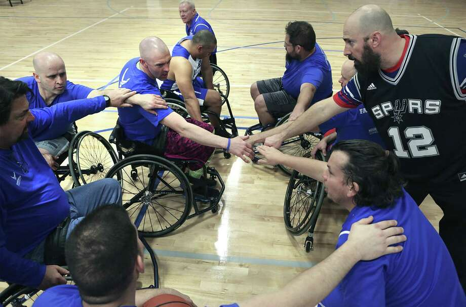 Members of one of the basketball teams playing an exhibition game huddle before the start of a game at the Air Force Wounded Warrior Program Warrior Care Event at Joint Base San Antonio-Randolph on Friday, Jan. 13, 2017. The CARE event provides seriously wounded, ill and injured military members, veterans and their caregivers focused and personalized service through caregiver support, training, adaptive and rehabilitative sports events. Photo: Bob Owen, STAFF / SAN ANTONIO EXPRESS-NEWS / © San Antonio Express-News