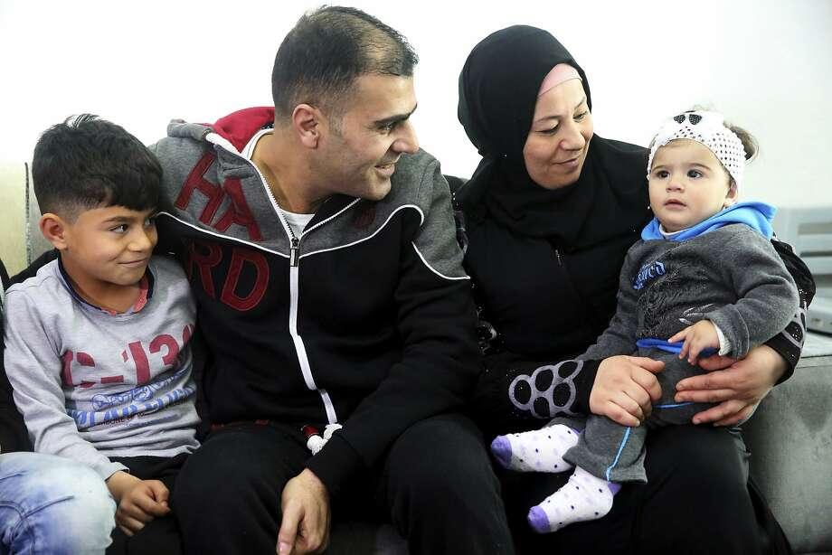 Ammar Sawan (center), 40, looks at the youngest of his four children, Sham, 1, in Amman, Jordan. Photo: Sam McNeil, Associated Press