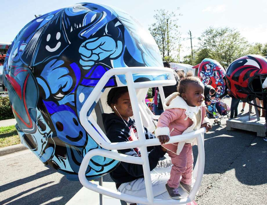 Timia Richardson and her young cousin, Taryn Francis, pose for a photo inside a helmet during a visit to Super Bowl Live at Discovery Green. Photo: Brett Coomer, Staff / © 2017 Houston Chronicle